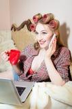 Het spreken op de mobiele slimme telefoon aantrekkelijke gelukkige glimlachende jonge bedrijfsvrouw die pret in bed in pyjama's h Stock Afbeelding