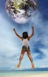 Het springen aan de planeet op strand stock fotografie