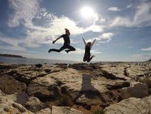 Het springen bij Strand Stock Foto's