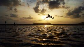 Het springen door zonsondergang bij meer Stock Afbeelding