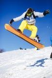 Het springen snowboarder op blauwe hemelachtergrond royalty-vrije stock afbeeldingen