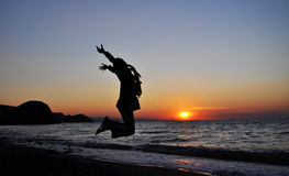 Het springen tijdens zonsopgang over het overzees royalty-vrije stock foto's