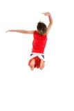 Het springen van de jongen de wapens in grande stellen. stock foto