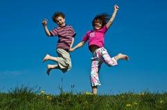 Het springen van het meisje en van de jongen Stock Afbeeldingen