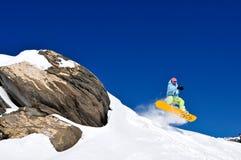 Het springen van Snowboarder van klip bij verse sneeuw Stock Afbeelding