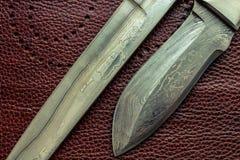 Het staalbladen van Damascus De jacht knifes Bruine achtergrond stock fotografie