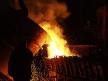 Het staalproductie van de staalwerken Gesmolten, gloeiend, geel, wit, metaalplavitsya de vlieg van brandvonken arbeider in helm Stock Afbeelding