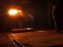 Het staalproductie van de staalwerken Gesmolten, gloeiend, geel, wit, metaalplavitsya ognennye vonkenvlieg arbeider in helm Stock Foto's