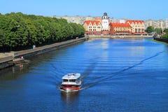 Het stadslandschap, de toeristenboot drijft onderaan de rivier Pregolya tegen het Vissendorp in Kaliningrad Stock Afbeeldingen