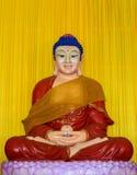 Het standbeeld die van Boedha een rode robe dragen Stock Afbeeldingen