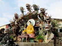 Het standbeeld van Boedha dressid in geel met draken Stock Afbeelding