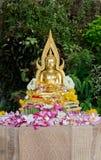 Het standbeeld van Boedha met bloembloemblaadjes wordt behandeld na het zijn gereinigde die Royalty-vrije Stock Afbeeldingen