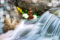 Het standbeeld van Boedha met bloemen op een kreek Stock Afbeeldingen