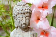 Het standbeeld van Boedha met een bloemachtergrond Royalty-vrije Stock Afbeeldingen