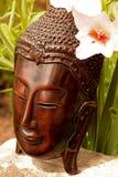 Het standbeeld van Boedha met een bloemachtergrond Stock Fotografie