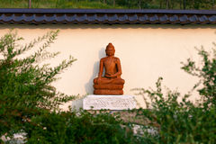 Het standbeeld van Boedha onder de groene takken in een tuin van stenen Royalty-vrije Stock Foto's