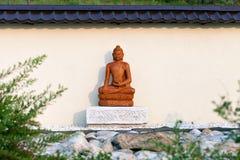Het standbeeld van Boedha onder de groene takken in een tuin van stenen Stock Afbeelding