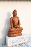 Het standbeeld van Boedha onder de groene takken in een tuin van stenen Stock Foto