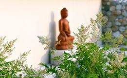 Het standbeeld van Boedha onder de groene takken in een tuin van stenen Royalty-vrije Stock Fotografie