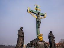 het standbeeld van de de 17de Eeuwkruisiging met Hebreeër die blauwe hemel in Charles Bridge Prague, Tsjechische Republiek van le royalty-vrije stock afbeeldingen