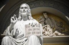Het standbeeld van Jesus met het citaatboek stock foto's