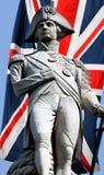 Het standbeeld van Nelson over Union Jack Stock Foto