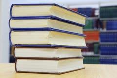 Het stapelen van boeken op bibliotheeklijst royalty-vrije stock foto's