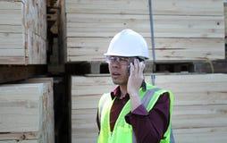 Het stapelen van hout en werkman Royalty-vrije Stock Afbeeldingen