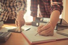 Het startteam schrijft nota van bedrijfsgegevens op notitieboekje royalty-vrije stock foto