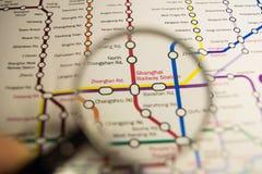 Het Stationmetro van Shanghai post op een gedrukte metro van Parijs kaart onder een meer magnifier lens stock afbeeldingen