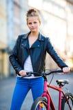 Het stedelijke biking - jonge vrouw en fiets in stad Stock Afbeeldingen