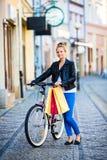 Het stedelijke biking - jonge vrouw en fiets in stad Royalty-vrije Stock Foto's