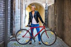 Het stedelijke biking - jonge vrouw en fiets in stad Royalty-vrije Stock Afbeeldingen