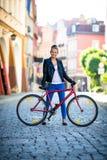 Het stedelijke biking - jonge vrouw en fiets in stad Stock Afbeelding