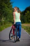 Het stedelijke biking - jonge vrouw en fiets in stad Stock Fotografie