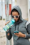 Het stedelijke drinkwater van de geschiktheidsvrouw en gebruikend smartphone royalty-vrije stock foto