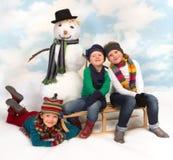 Het stellen rond de sneeuwman Stock Afbeelding