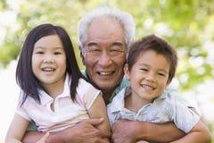 Het stellen van de grootvader met kleinkinderen Stock Afbeeldingen