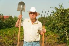 Het stellen van de tuinman met zijn vork en schop Royalty-vrije Stock Fotografie