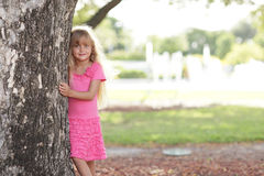 Het stellen van het meisje achter de boom Stock Afbeelding
