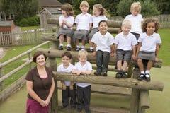 Het stellen van kinderen en van de Leraar voor klassenfoto Stock Afbeelding
