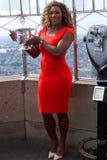 Het stellen van Serena Williams van de US Open 2014 kampioen met US Opentrofee op de bovenkant van de bouw van de Imperiumstaat Stock Fotografie