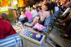 Het stemmen van over apparaat ligt op knie in auditorium Royalty-vrije Stock Foto's