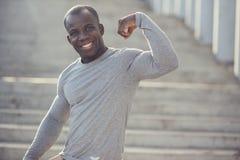 Het sterke Atletische Model die van de Mensengeschiktheid zijn bicepsen tonen Stock Afbeelding