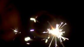Het sterretje fonkelt in dark met vele heldere ixora en verlicht het silhouet van het meisje die op de lichten letten stock video