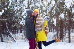 het sterretje in handen van het jonge mooie man en vrouwen kussen en viert de wintervakantie in sneeuwbos stock foto