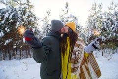 het sterretje in handen van het jonge mooie man en vrouwen kussen en viert de wintervakantie in sneeuwbos royalty-vrije stock foto's