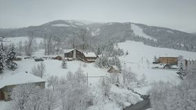 Het stijgen boven een dorp in Karpatische bergen De mening van het vogel` s oog van snow-covered huizen in bergen Landelijk lands stock videobeelden