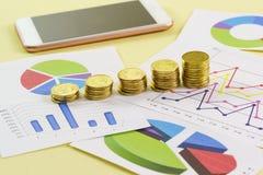 Het stijgen in de grootte van de stapel gouden muntstukken is op gekleurde grafieken Voorbereiding van het rapport aan investeerd royalty-vrije stock afbeeldingen