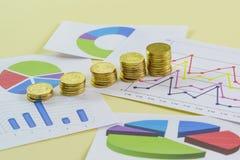 Het stijgen in groottestapels van gouden muntstukken en gekleurde grafiek op een gele achtergrond Voorbereiding van het rapport a stock foto
